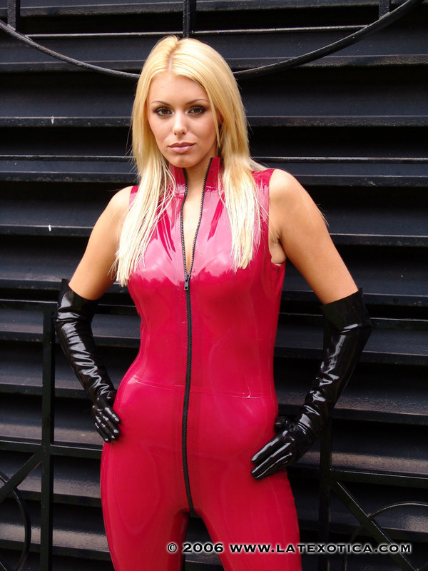 charming female Alicia in red latex jumpsuit & boots